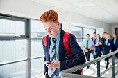 Teenage redhead male using phone in the corridor at school.