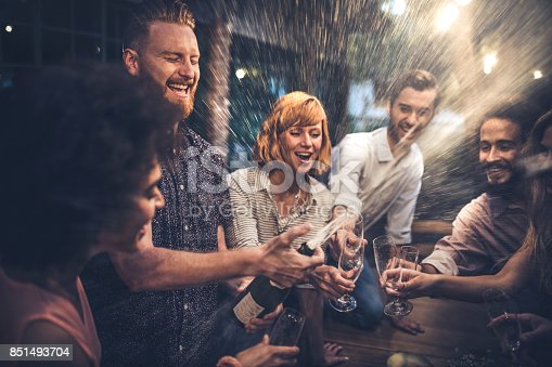 Young man splashing while opening champagne on a night party with his friend.