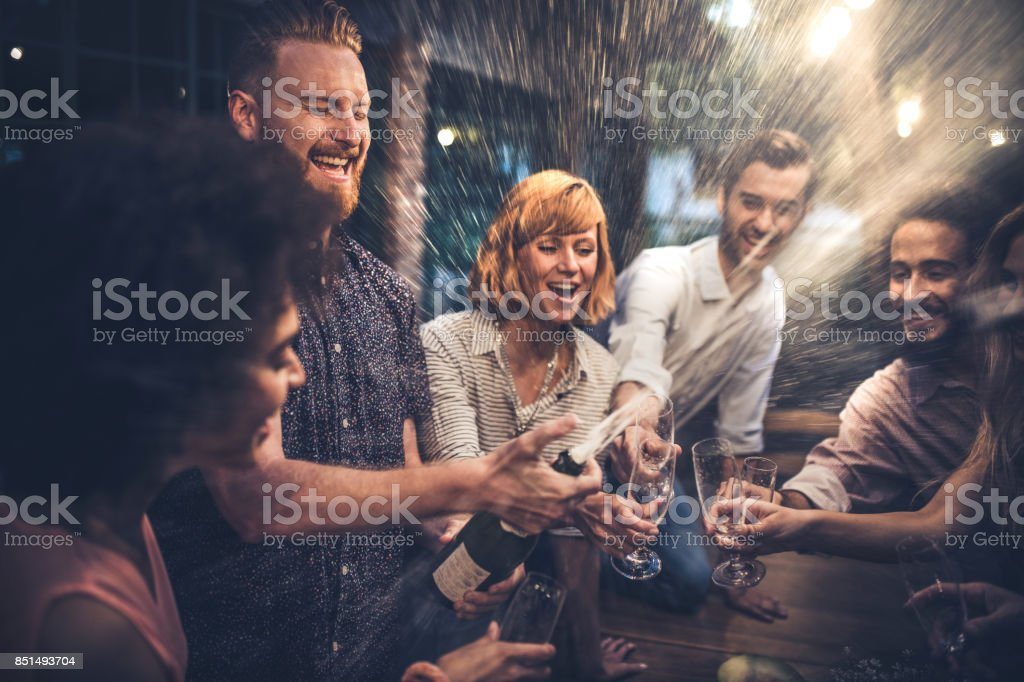 Redhead man opening a champagne on a party with his friends. stock photo