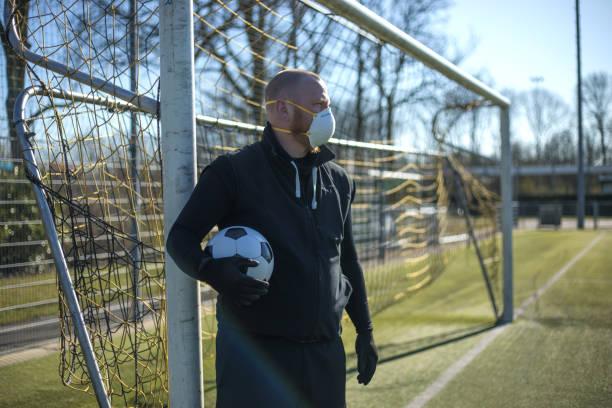 Rothaariger Mann trägt eine Gesichtsmaske und hält einen Fußball in einem Fußballkomplex – Foto