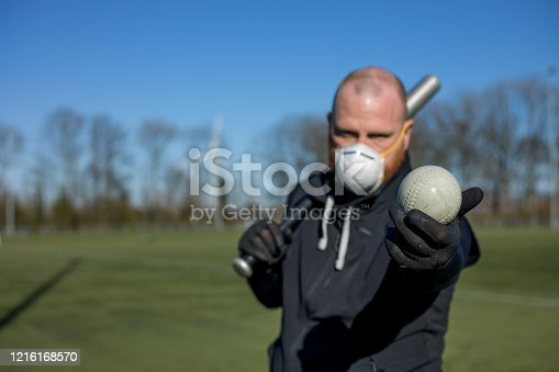 Redhead man wearing a face mask and holding baseball equipment to symbolise the delayed, postponed and cancelled baseball and softball competitions due to the corona Covid-19 virus outbreak