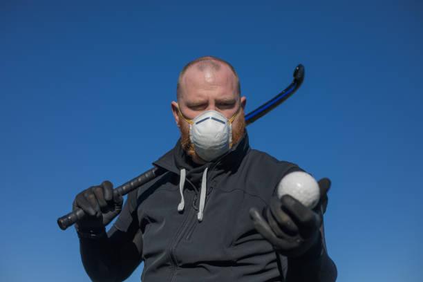 roodharige mens die een gezichtsmasker draagt en hockeymateriaal houdt - dutch hockey stockfoto's en -beelden