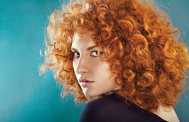 redhead sexy curly young woman - krause haare stock-fotos und bilder