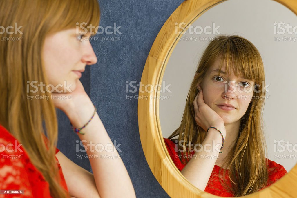 Redhead teenage girl looking in mirror stock photo