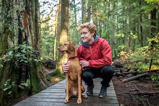 Redhead Teenaged Boy with Vizsla Dog Resting on Forest Boardwalk