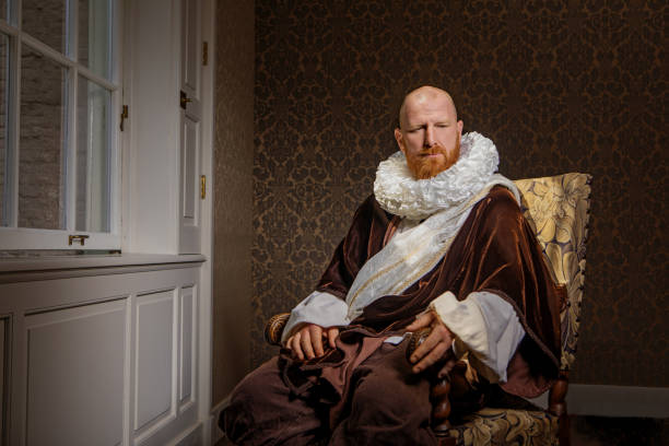 Redhead traditional dutch man reading a book by candlelight Handsome redhead traditional dutch man wearing historically correct outfit reading a book by candlelight in a typical townhouse drawing room renaissance stock pictures, royalty-free photos & images
