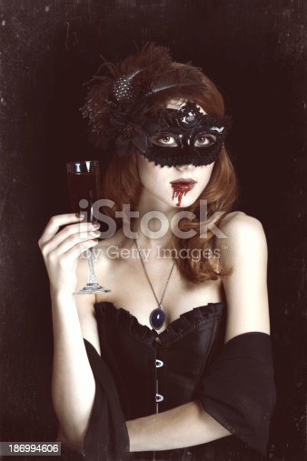 Redhead vampire woman with glass of blood. Photo in vintage style.