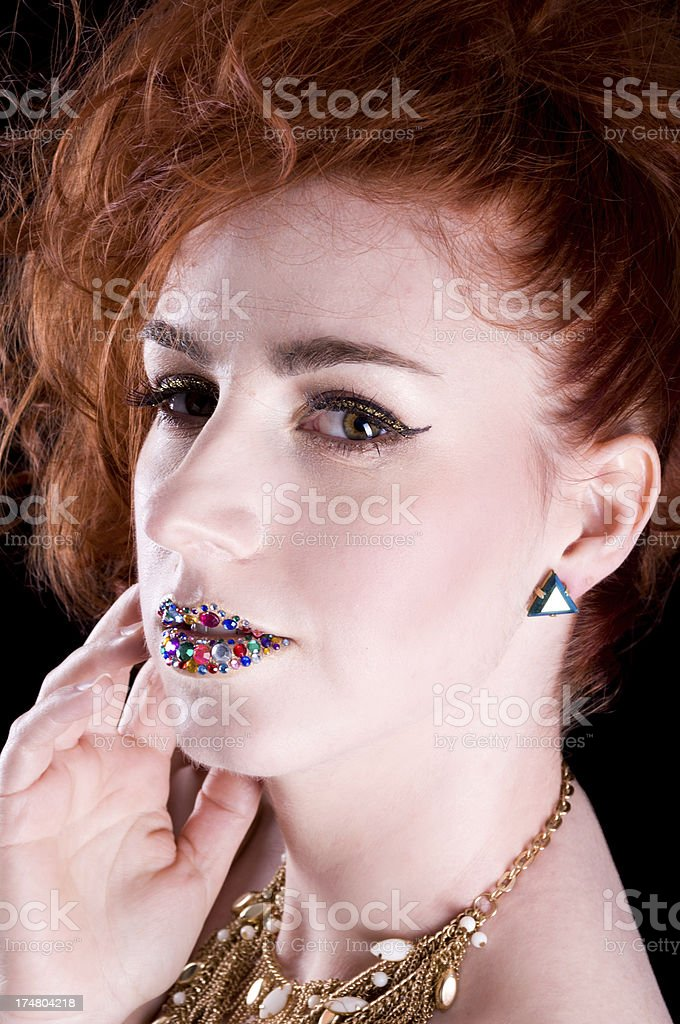 Redhead with jeweled lips touching face. royalty-free stock photo