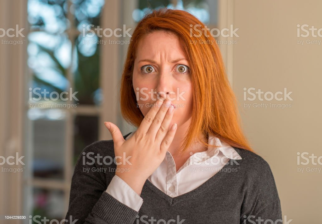 Redhead woman at home cover mouth with hand shocked with shame for...