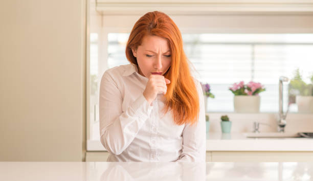 redhead woman at kitchen feeling unwell and coughing as symptom for cold or bronchitis. healthcare concept. - tossire foto e immagini stock
