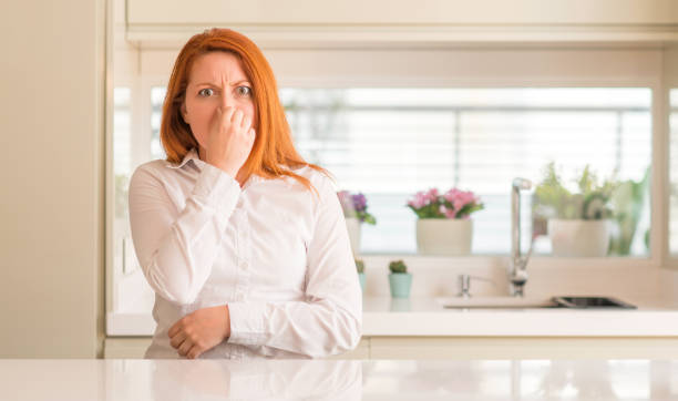 redhead woman at kitchen smelling something stinky and disgusting, intolerable smell, holding breath with fingers on nose. bad smells concept. - annusare foto e immagini stock