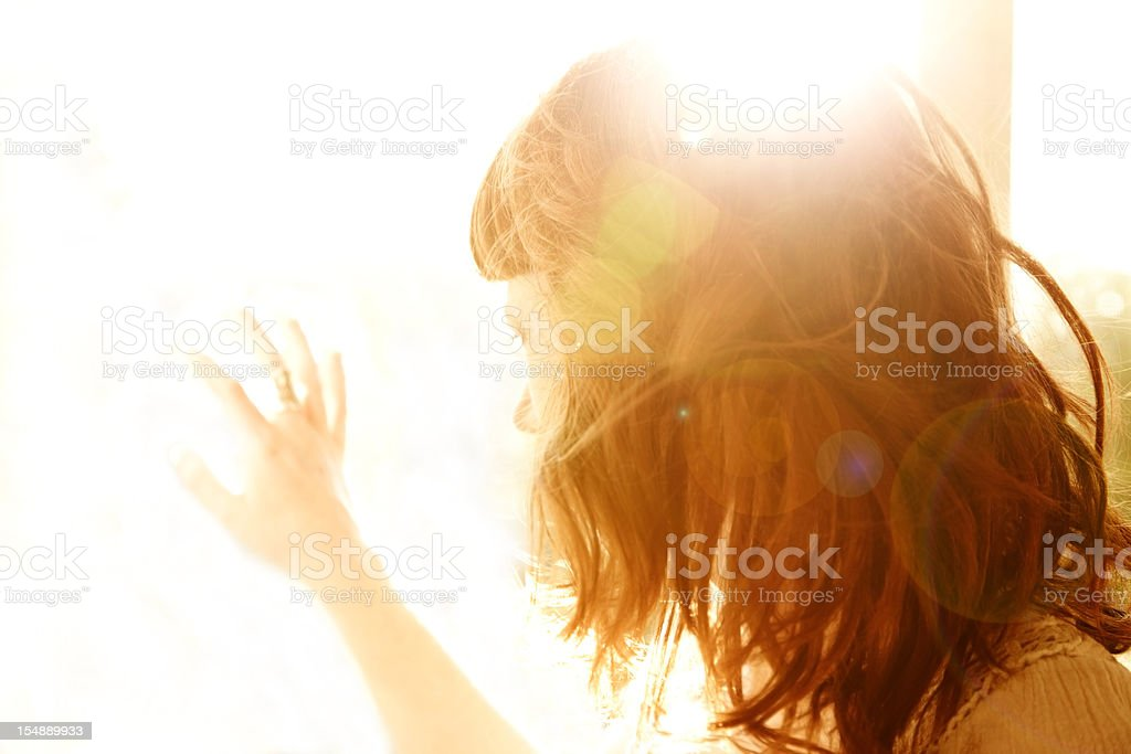 Redhead woman backlit by sun with hand on glass window stock photo