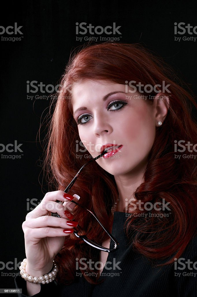 Redhead woman business outfit glasses in mouth royalty-free stock photo