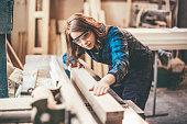 Redhead woman cutting a plank