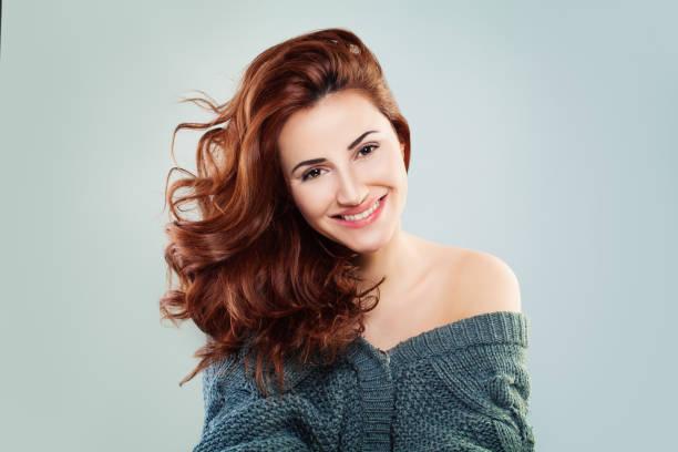 rothaarige frau mode modell lächelnd. hübsches mädchen auf grauem hintergrund - dauerwelle stock-fotos und bilder
