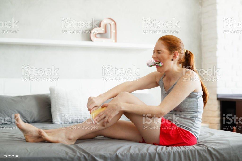 Redhead Woman Feeling Pain Waxing Her Legs stock photo