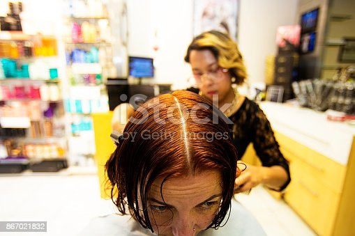 696318954 istock photo Redhead woman has  her hair cut at a solon by a hairdresser 867021832