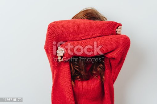 Redhead woman in a colorful red outfit standing hiding her face with her arms over white