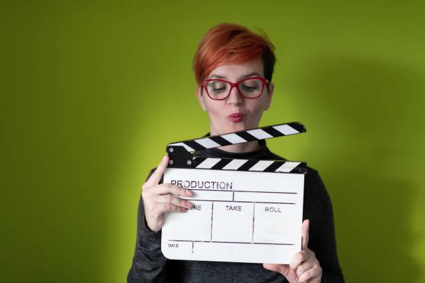 Rothaarige Frau hält Film Klatscher auf grünem Hintergrund – Foto
