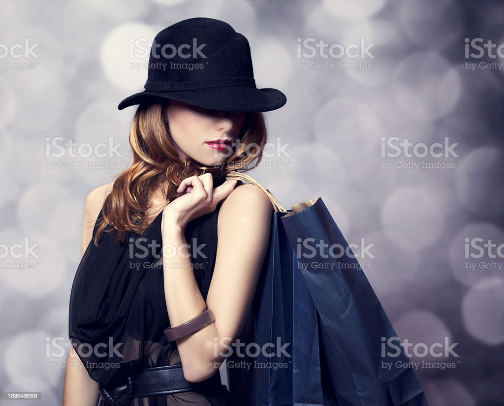 Redhead woman in hat with shopping bags stock photo