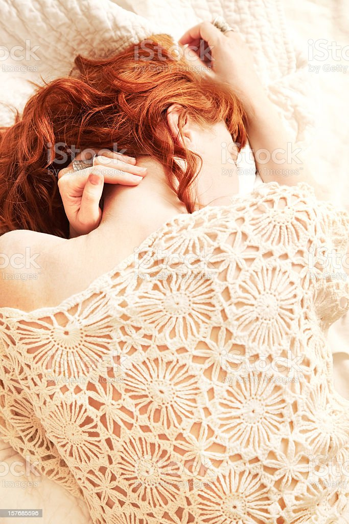 Redhead woman lying in bed with face obscured stock photo