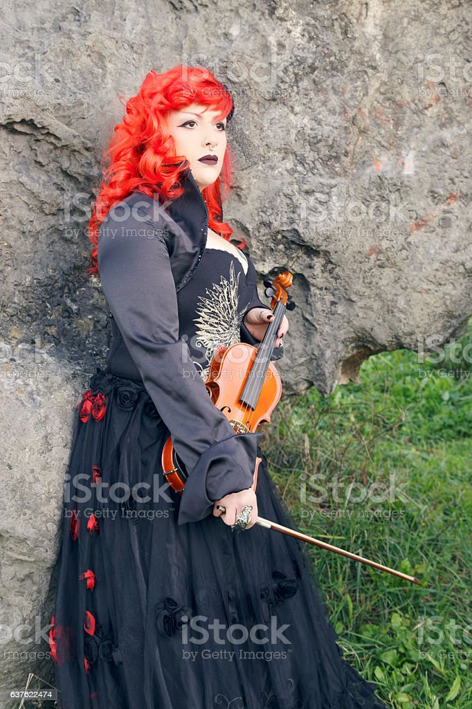 Redhead woman playing violin outdoors. stock photo