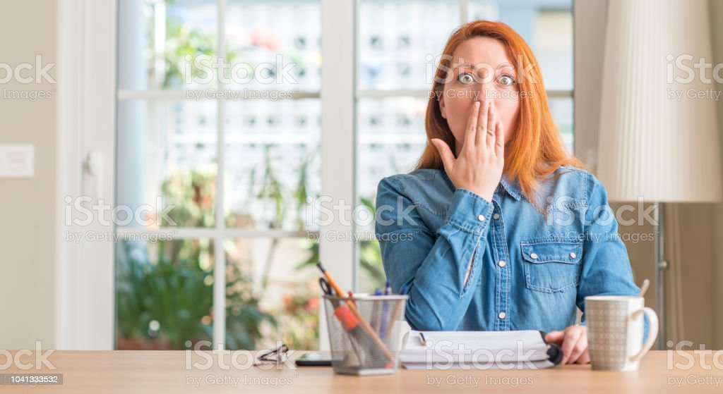 Redhead woman studying at home cover mouth with hand shocked with...