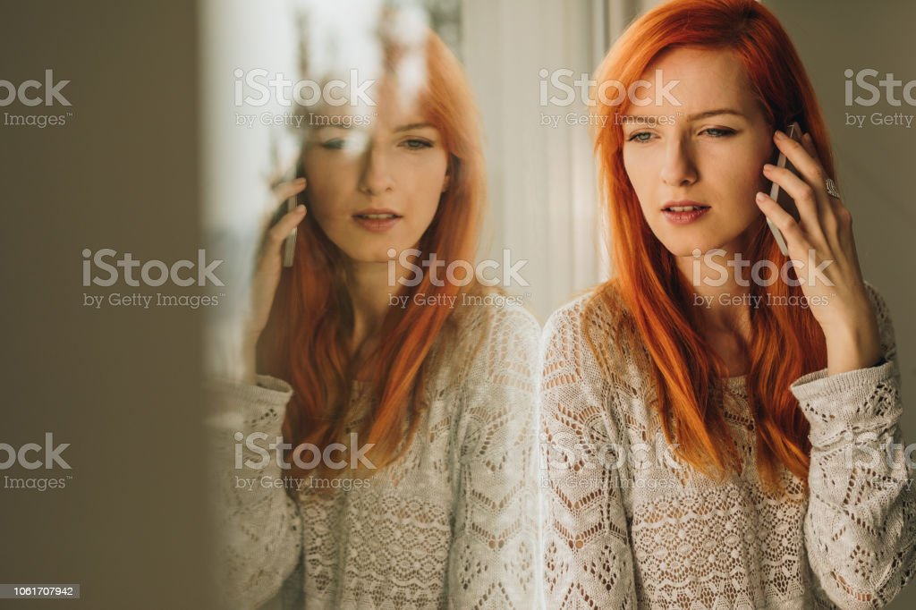 Young red-haired woman communicating with someone over cell phone and...