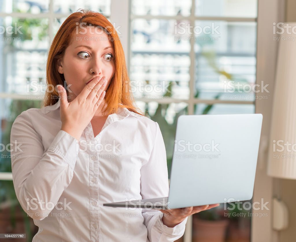 Redhead woman using computer laptop at home cover mouth with hand...