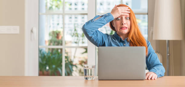Redhead woman using computer laptop at home stressed with hand on head, shocked with shame and surprise face, angry and frustrated. Fear and upset for mistake. Redhead woman using computer laptop at home stressed with hand on head, shocked with shame and surprise face, angry and frustrated. Fear and upset for mistake. shocked computer stock pictures, royalty-free photos & images
