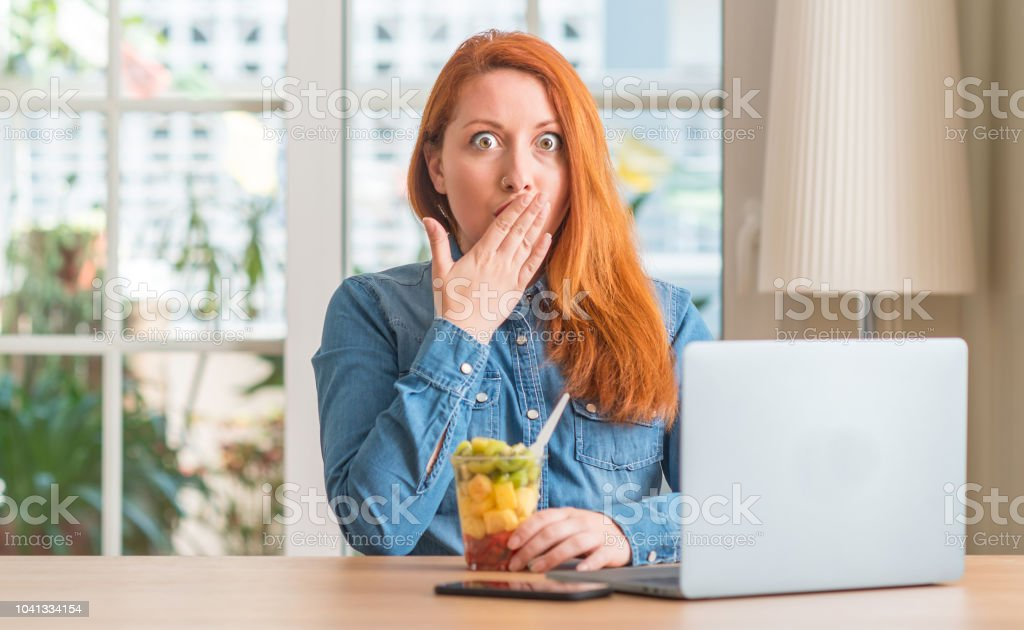Redhead woman using computer laptop eating fruit at home cover mouth...