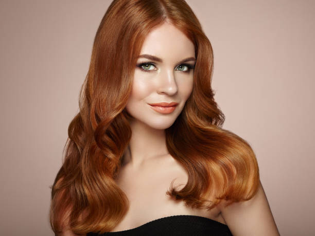 Redhead woman with curly hair Redhead Girl with Long Healthy and Shiny Curly Hair. Care and Beauty. Beautiful Model Woman with Wavy Hairstyle. Make-Up and Black Dress redhead stock pictures, royalty-free photos & images