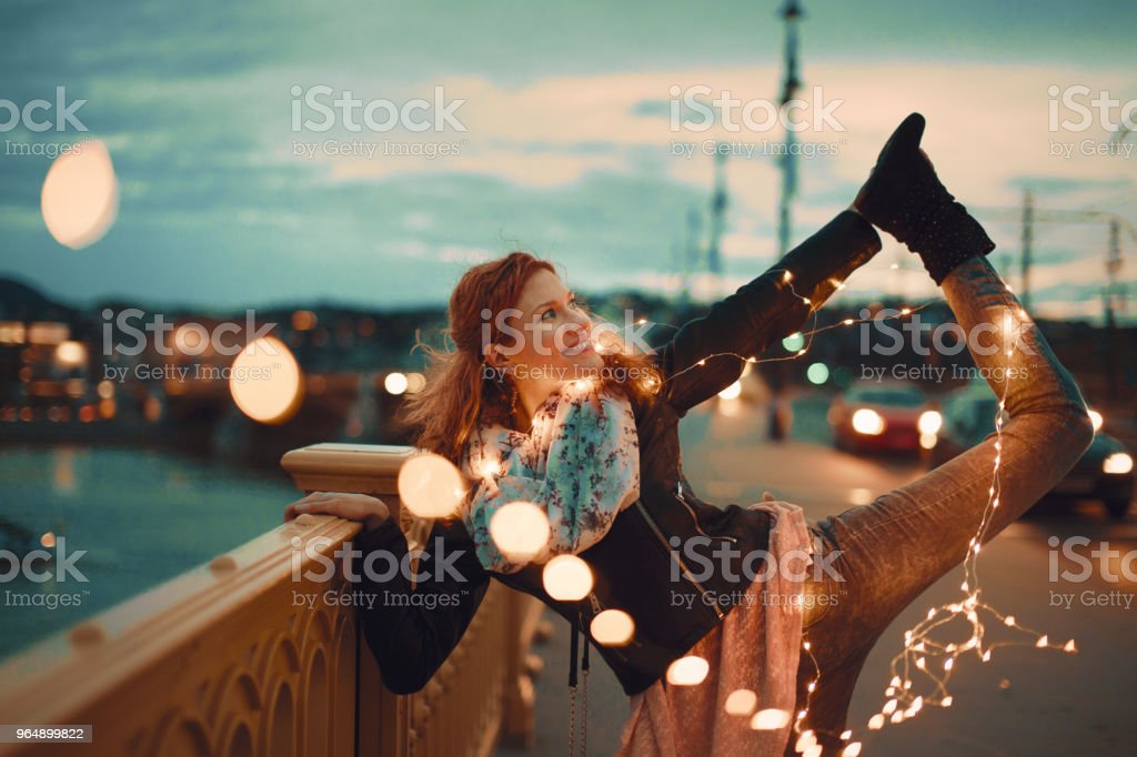 Redhead woman with garland fairy lights doing yoga vintage style royalty-free stock photo