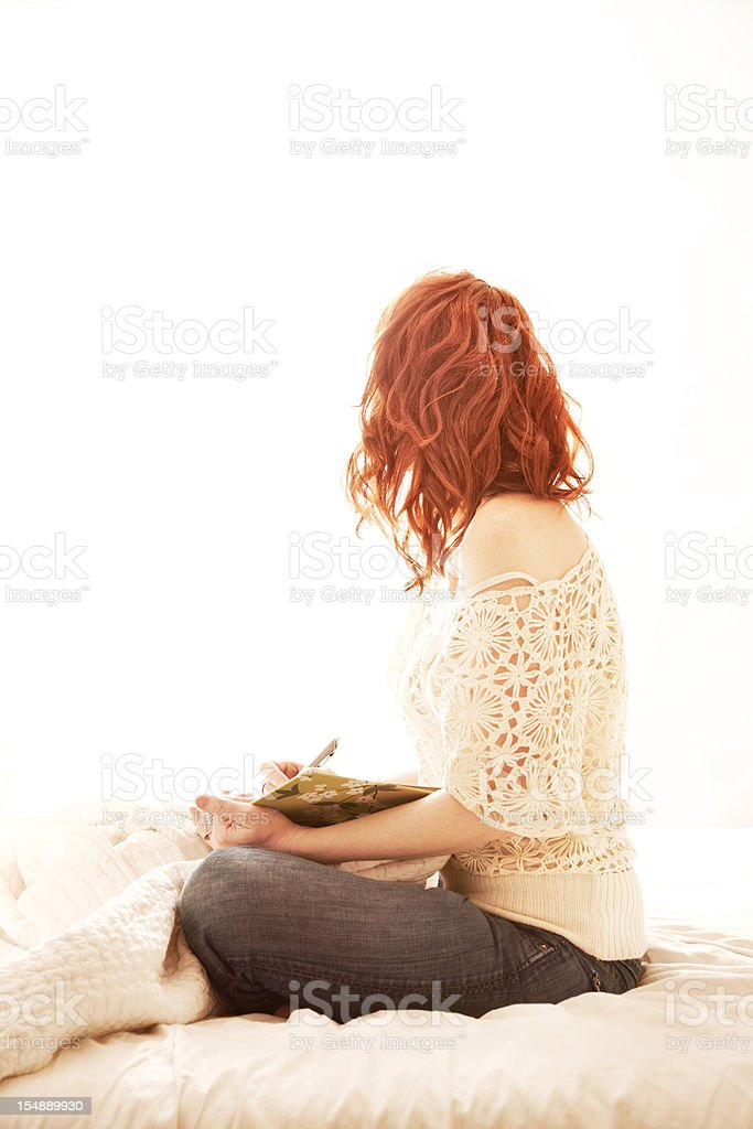 Redhead woman writing sitting in bed stock photo
