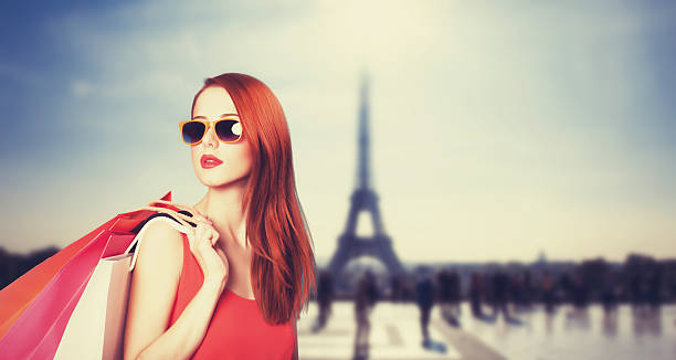 redhead women with shopping bags on parisian background. - paris fashion stock photos and pictures
