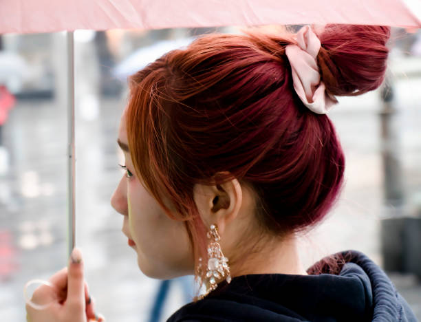 Redhead young Asian woman walking under umbrella on a rainy day