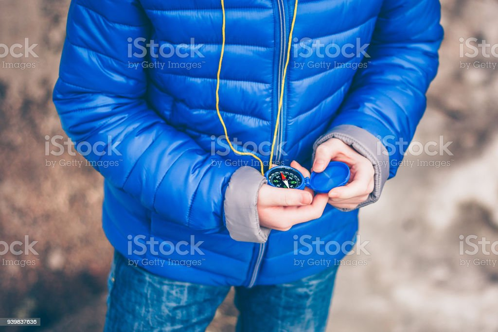 A redheaded boy travels and explores with a compass in his hand, a young discoverer stock photo