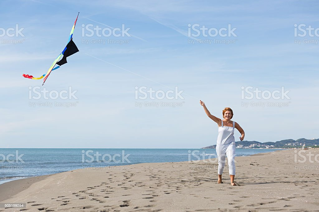 redheaded model holding kite and posing stock photo