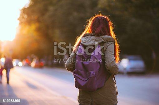 istock Redheaded Student Girl Waiting Public Transportation 615983356