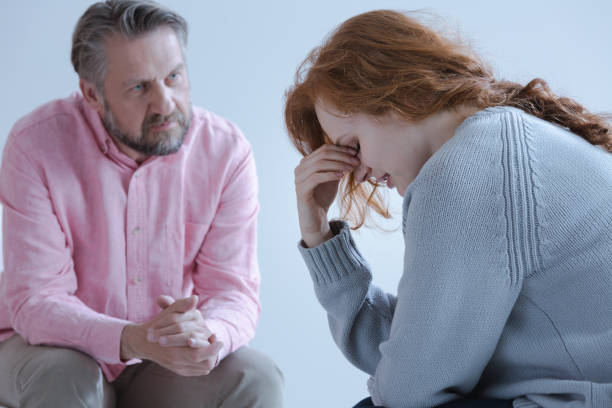 A redheaded young woman with a post traumatic stress disorder A redheaded young woman with a post traumatic stress disorder touching her eyes with her hand during an individual psychotherapy session with a specialist. low self esteem stock pictures, royalty-free photos & images