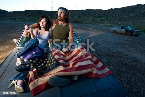 Redneck couple watching the sunset on top of car with copy-space