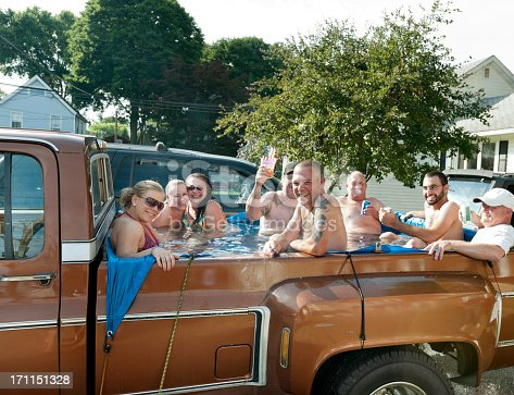 Eight people having fun in the back of a pick-up truck filled with water.