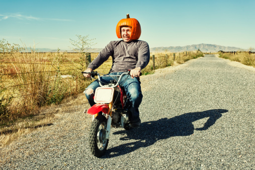 Photo of a man riding a miniature dirt bike with a helmet carved out of a pumpkin.