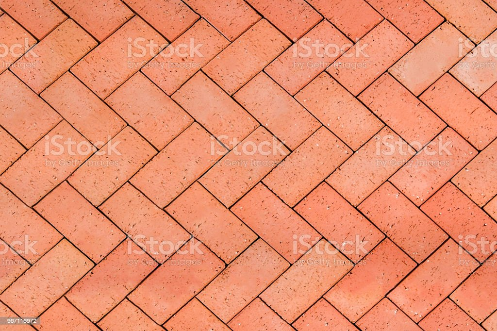 Red-Orange bricks tiled floor with zigzag pattern texture background stock photo