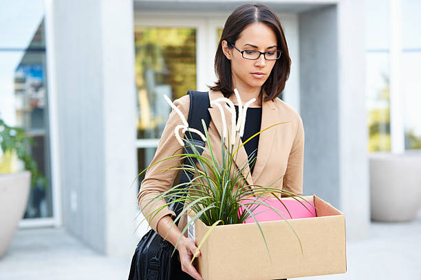 Redundant Businesswoman Leaving Office With Box Redundant Businesswoman Leaving Office With Box Looking Down Upset downsizing unemployment stock pictures, royalty-free photos & images
