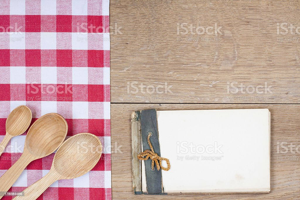 Red-white kitchen tablecloth, wooden spoons, old notepad on wood royalty-free stock photo