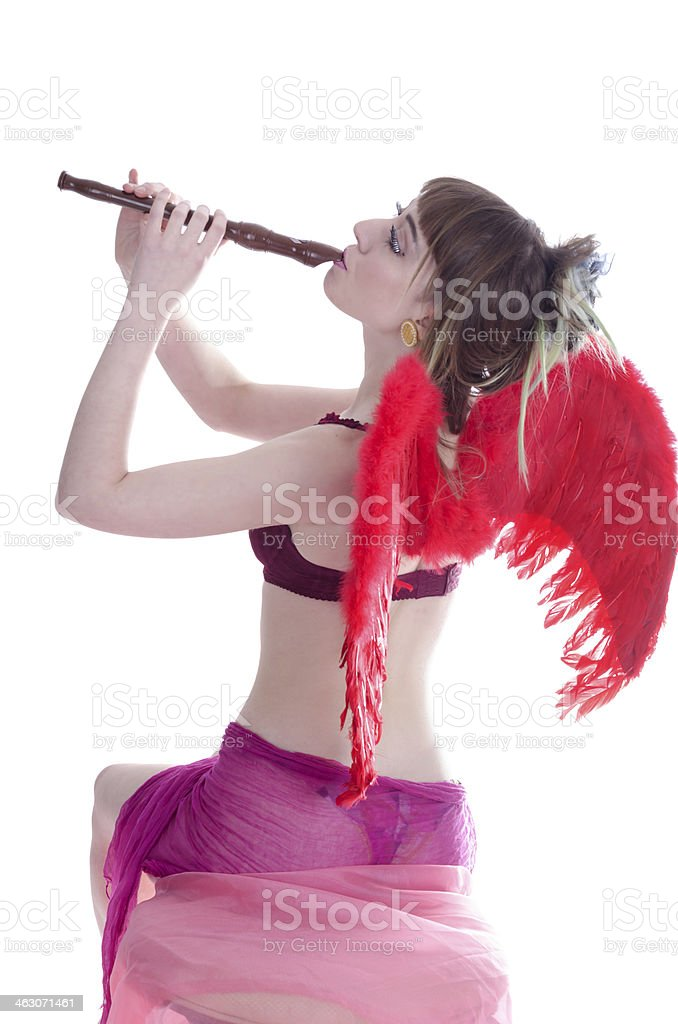 Red-winged cherub leaning back playing recorder. royalty-free stock photo