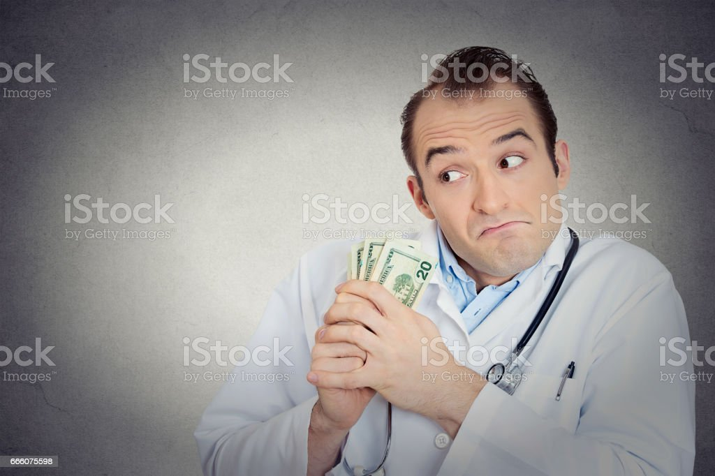 reedy miserly health care professional, male doctor holding, protecting his money dollars in hand stock photo