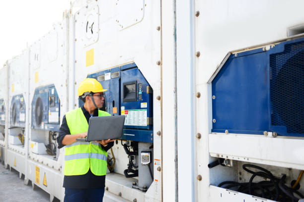 Reefer container technician is using laptop for monitoring temperature of frozen & chill shipments. stock photo
