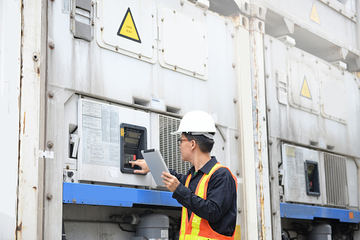 istock Reefer container technician is using tablet for monitoring temperature of frozen & chill shipments. 871601756